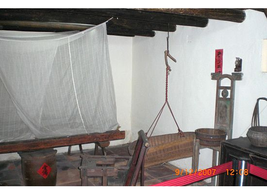 On the right hand side of the living room, there is a bedroom with drapes on top of the bed to block the bugs. Underneath the bed, there is a earthen container. It is for rice. On top of it, there is a piece of red paper with 2 Chinese characters that have the meaning