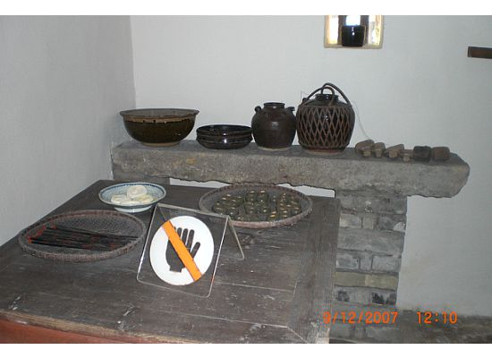 On your left in the same room, is the dining table with some utensils, such as chopsticks, bowl, plate and wine bottle.