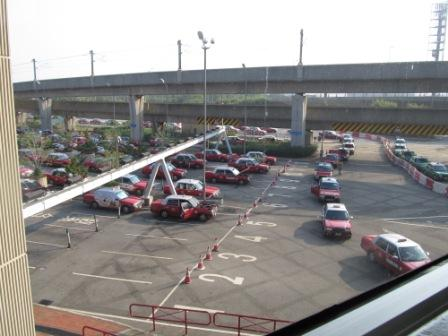 These taxis are waiting for their customers at the Hong Kong International Airport.  See the right corner, there is a line of green taxis for going to the New Territories.  The red ones definitely dominate the market