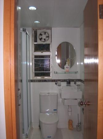This is the bathroom. On the left hand side, it was a built-in cabinet. A space for washing machine and dryer on top of each other. Then, a stand-up shower.